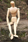 Wooden pose puppet sitting on stone — Zdjęcie stockowe