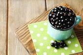 Ripe blackcurrants in mug on board — Stock Photo