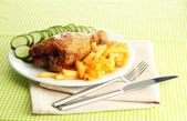 Roast chicken with french fries and cucumbers, on green table cloth — Stock Photo