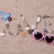 Word love made from sea shells and stones on sand — Stock Photo #49143423