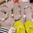 Word sun made from sea shells and stones on sand with beach accessories — Stock Photo #49143431