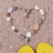 Shape of heart made from sea shells and stones on sand with beach accessories — Stock Photo #49143439