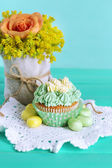 Tasty cupcake on table, on turquoise background — Stock Photo