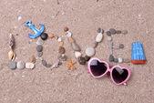Woord liefde gemaakt van zeeschelpen en stenen op zand — Stockfoto