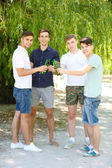 Handsome young men with beer in park — Stock Photo