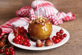 Sweet caramel apple on stick with berries — Stock Photo