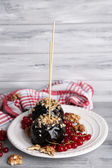 Sweet caramel apples on sticks with berries — Stock Photo