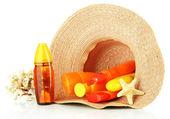 Bottles with suntan cream in hat — Stock Photo