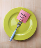 Paper with message attached to fork, on plate — Stock Photo