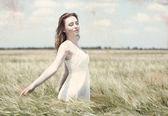 Beautiful young woman in field — Stock Photo