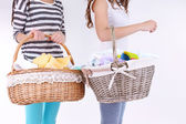 Women holding laundry baskets with clean clothes — Stock Photo