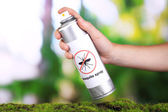 Hand holding mosquito spray on nature background — Stock Photo