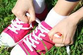 Young woman tying shoelace — Photo