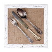 Wooden frame and vintage cutlery — Stock Photo