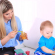 Young pretty mother feeding her son on sofa in room — Stock Photo #49188561
