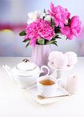 Peonies in vase, tea and marshmallow — Stock Photo