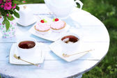Coffee table with teacups and cakes — Stock Photo