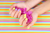 Female hand with colorful nails holding decorative stones — Stock Photo