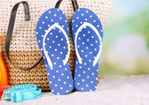 Summer wicker bag with accessories on sand — Stock Photo