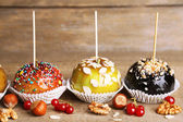 Sweet caramel apples on sticks with berries, on wooden table — Stock Photo