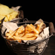 Tasty french fries in metal basket and potato chips on wooden table with dark light — Stock Photo #49207595