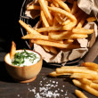 Tasty french fries in metal basket on wooden table with dark light — Stock Photo #49207599