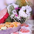 Present box with sweets and flowers on table on bright background — Stock Photo #49207971