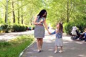 Gelukkig moeder en dochter. wandelen in het groene park — Stockfoto