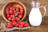 Ripe sweet strawberries in wooden bowl and jug with milk on color wooden background — Stock Photo