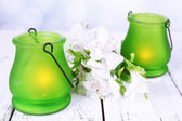 Bright icon-lamps with flowers on table on bright background — Stok fotoğraf