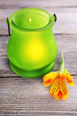 Bright icon-lamp with flower on wooden background — Stock Photo