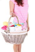 Woman holding laundry basket with clean clothes, towels and pins, isolated on white — Stock Photo