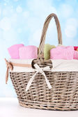 Colorful towels in basket, on table, on bright background — Stock Photo