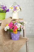 Bouquet of flowers in decorative buckets — Stock Photo