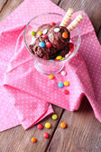 Chocolate ice cream with multicolor candies and wafer rolls in glass bowl, on wooden background — Stock Photo