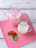 Glass jug of milk cocktail with raspberry taste on wooden table, on light background — Stock Photo
