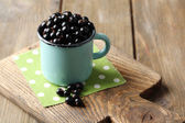 Ripe blackcurrants in mug on board, on wooden background. — Stock Photo
