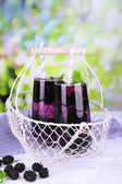 Tasty cool blackberry lemonade with ice on wooden table, on nature background — Stock Photo