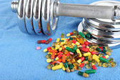 Dumbbell and colorful pills, tablets, on color background — Stock Photo