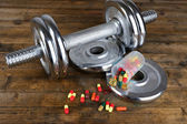 Dumbbell and colorful pills, tablets, on wooden background — Stock Photo
