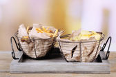 Tasty potato chips and french fries in metal baskets on wooden table, on light background — Stock Photo