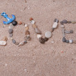 Word love made from sea shells and stones on sand — Stock Photo #49259255