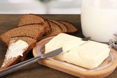 Butter on wooden holder surrounded by bread and milk on wooden table on window background — Stock Photo