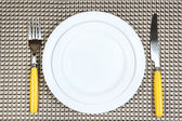 Knife, color plate and fork, on color background — Foto de Stock