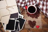 Composizione con tazza di caffè, cuori decorativi, plaid spezie e vecchie foto in bianche, su fondo in legno — Foto Stock