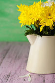 Beautiful chrysanthemum flowers in pitcher on wooden table — Stock Photo