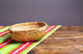 Empty wicker basket on wooden table, on dark background — Stock Photo