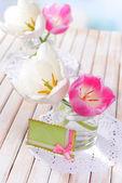 Lindas tulipas no balde em um vaso na mesa de luz de fundo — Fotografia Stock