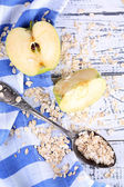 Apple with oatmeal and vintage spoons on napkin, on color wooden background — Stock Photo