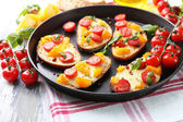 Tasty bruschetta with tomatoes on pan, on old wooden table — Stock Photo